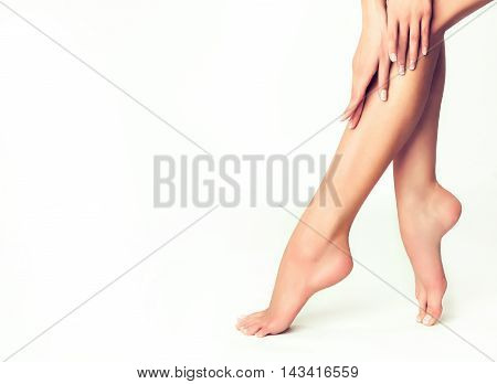 Beautiful well-groomed female legs . Foot care . Epilation and depilation of hair on the feet . Smooth long slender bare foot .