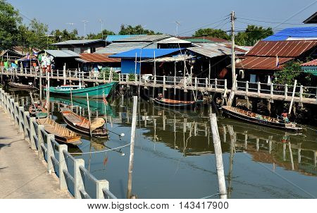 Samut Songkhram Thailand - December 29 2011: Old wooden fishing boats moored to walkways dock in front of a cluster of Thai houses at a small fishing village nestled on the banks of an estuary