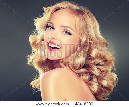 Beautiful girl with long wavy hair. Blonde model woman with curly hairstyle .