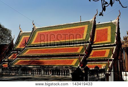 Saraburi Thailand - January 8 2013: Colorful orange yellow and green interlocking gabled roofs with Chofah ornaments on the upper terrace Vihan hall at Wat Phra Phutthabat