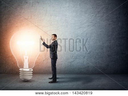 Businessman stands touching big glowing light bulb. Ideas nad concepts. Creativity and inspiration. Signs and symbols. Intellectual job. Business innovations.