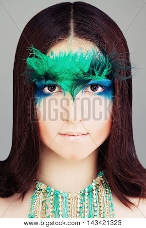 Yound Woman Fashion Model. Face with Makeup and Feather