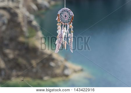 Handmade pink native american dream catcher on background of rocks and lake. Tribal elements feathers shells lace