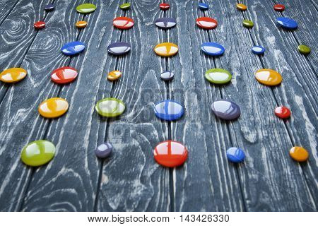 A Set Of Colorful Glass Buttons For Clothes On A Dark Wooden Background