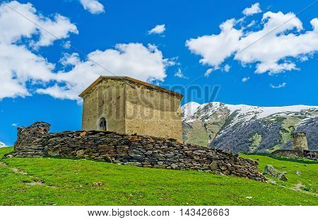 The medieval Jgrag (St George) church surrounded with the stone fence Ushguli Upper Svaneti Georgia.