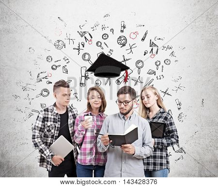 University students standing near concrete wall with sketches on it with graduation hat floating above them. Concept of finishing school and starting adult life.