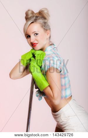 Sexy girl retro style with mop woman housewife cleaner in domestic role. Traditional sharing household chores. Pin up housework. Pink background