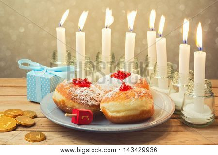 Jewish holiday Hanukkah celebration with donuts and candles