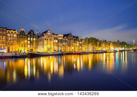 Night Amsterdam city view of Netherlands traditional houses with Amstel river in Amsterdam Netherlands