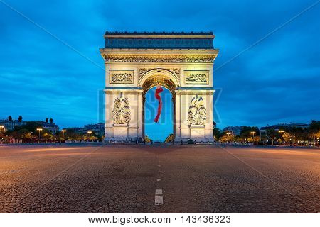 Arc de Triomphe Paris and Champs Elysees with a large France flag flying under the arch in Europe victory day at Paris France.