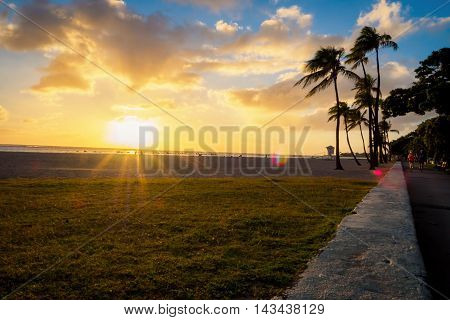 Honolulu, Hawaii, USA - Dec 21, 2015: Low angle setting sun over beach at Ala Moana Park, along Ala Moana Park Drive. The beach overlooks Mamala Bay and features some flares. From afar, two joggers appear on the right of image.