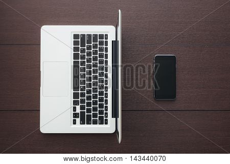 phone and laptop computer on table top view