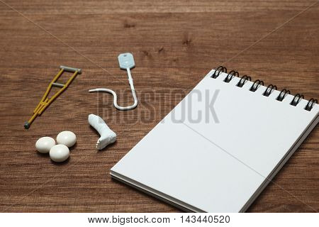 Miniature items of illness or injury beside memo pad. Injury, illness, medical, insurance concept.