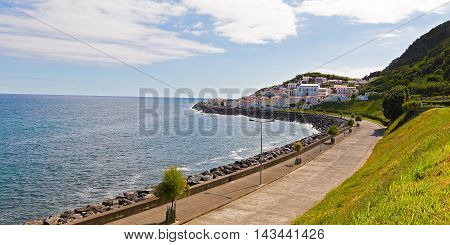 Atlantic Ocean coast and picturesque village at the mountain foot in Azores Portugal. Church and village houses on Sao Miguel Island in Azores Portugal.
