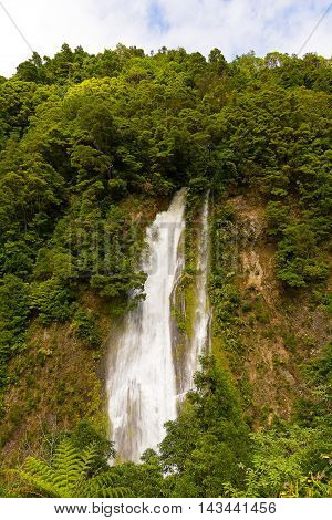Scenic waterfall near Furnas in Azores Portugal. Rain forest on a hill and waterfall in sight near a road from Furnas to Ribeira Quente on Sao Miguel Island.
