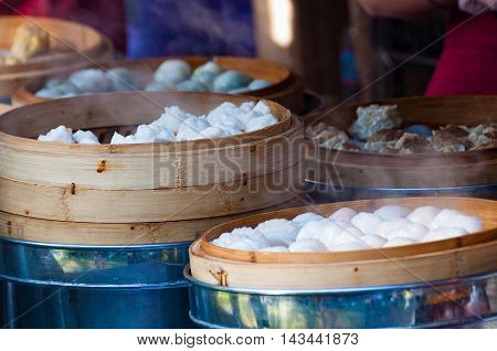 Asian street food. Steamed buns and meat on vendor stall during Sydney Night Noodle Market Festival. Selective focus shallow DOF
