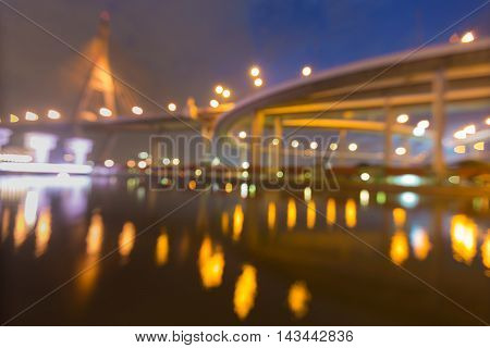 Blurred lights suspension bridge with reflection at twilight