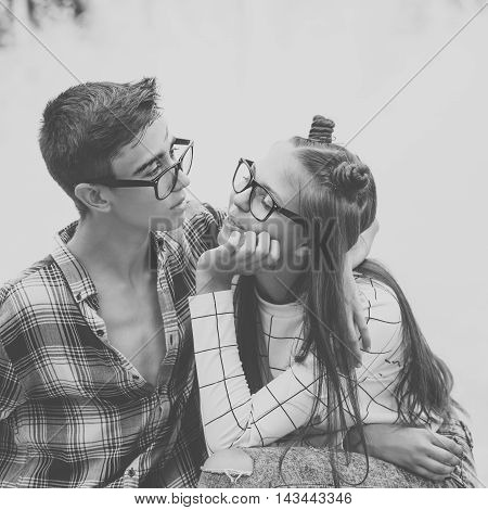 Loving couple teenagers. Girlfriend and boyfriend hugging. They wear glasses. Black and white photography. First love. He falls in love. Date.
