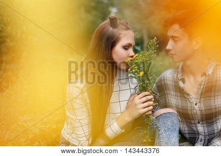 Loving couple teens together. Girlfriend and boyfriend together. The boy looks at the girl. Girl smelling a bouquet of wildflowers. Creative shooting. First love. He falls in love. Date.