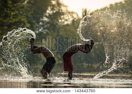 Children playing splashing water in the river.