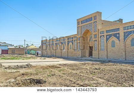 The portal decorated with the glazed tiles leads to Chorsu Bazaar Shakhrisabz Uzbekistan. poster