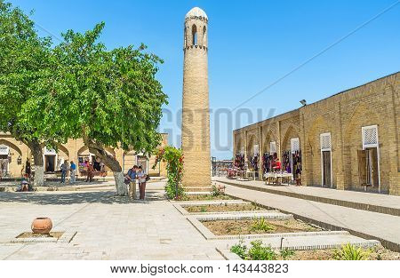 SHAKHRISABZ UZBEKISTAN - MAY 2 2015: The small brick minaret in the courtyard of Dorut Tilavat complex surrounded by the tourist market with a lot of handmade souvenirs on May 2 in Shakhrisabz.