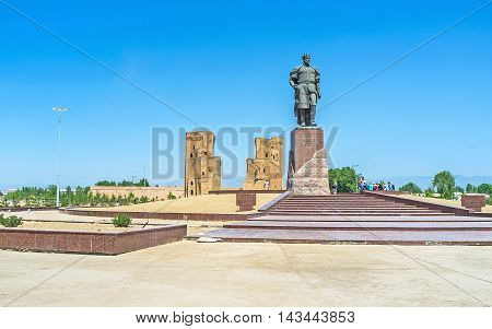 SHAKHRISABZ UZBEKISTAN - MAY 2 2015: The monument to the Turco-Mongol conqueror Amir Temur in the place of his birth with the ruins of Ak-Saray Palace on the background on May 2 in Shakhrisabz.