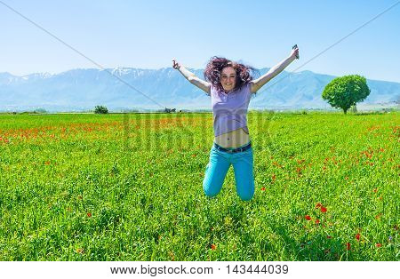 The young girl jumps on the poppy field and laughs Samarkand suburb Uzbekistan.