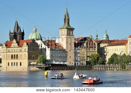 PRAGUE CZECH REPUBLIC - AUGUST 07 2016: People having fun with small boats on Vltava River on August 07 2016 in Prague. Prague is the capital and largest city of the Czech Republic