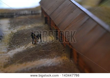 Man petting horse. Stable. Small world. Layout