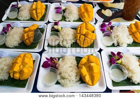 Asian snack sticky rice with mango. Market hawker stall with traditional street food