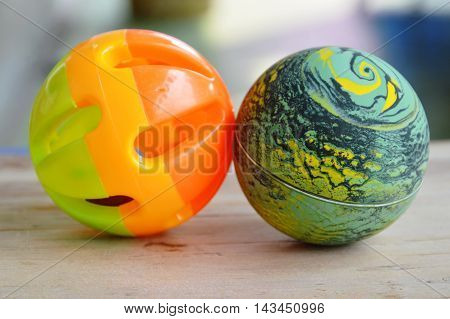 plastic and rubber pet toy ball on wooden board