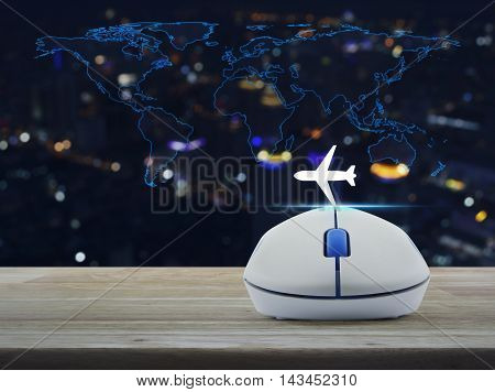 Wireless computer mouse with airplane icon on wooden table ovver world map and blur night city tower Airplane transportation concept Elements of this image furnished by NASA