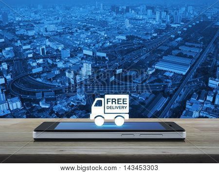 Free delivery truck icon on modern smart phone screen on wooden table over city tower street and expressway Transportation business concept
