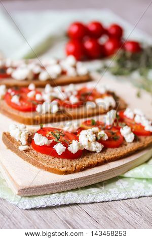 Fresh homemade crispy Italian antipasto called Bruschetta topped with cherry tomato, feta cheese and thyme on a wooden board, selective focus