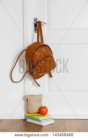 Schoolbag with lunch near door