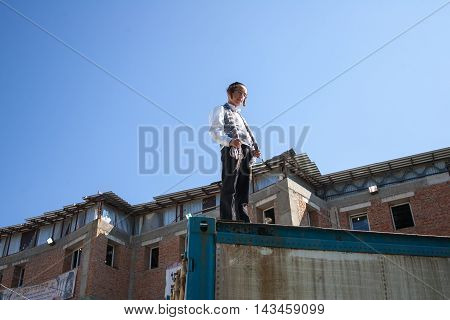 Uman, Ukraine - September 17 2015: Jewish boy stands on the fence during celebration of Rosh Hashanah, the Jewish New Year. City of Uman is a pilgrimage site and the burial place of Jewish spiritual leader Rebbe Nachman, a great grandson of the founder of