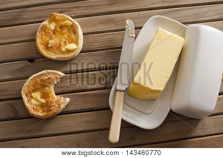 One yellow stick of butter on tray with knife besides two toasted english muffins on wood slat table