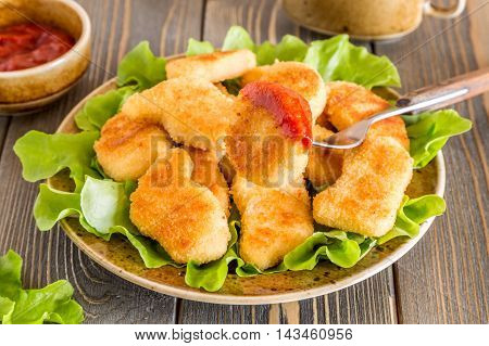 Chicken nuggets with ketchup and salad, selective focus.