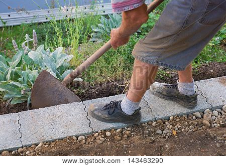 senior gardener build a wall fundament in the garden