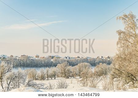 Russian Winter. January snow-covered landscape of the ravine on a background of low-rise housing
