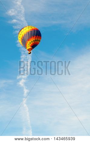 Colorful Hot Air Balloon in Flight with blue sky in background