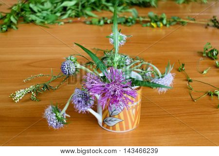 bouquet of wild flowers in a cup burr clover