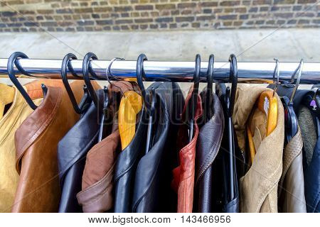 First person view of leather jackets on rack for sale in outdoor market with brick and sidewalk background
