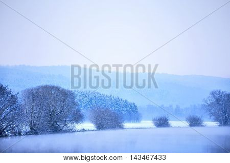 Winter landscape with fog over a river and bare trees at blue hour.