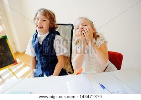 Funny little schoolchildren boy and girl sit at one desk. It's elementary school students. Children laugh. On the desk in children are school supplies and textbooks. Back to school.