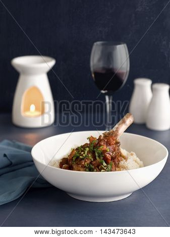 Braised lamb shanks with candle and glass of wine.