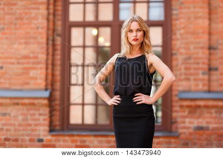 Fashionable blonde in black clothes, with arms akimbo against window of brick building