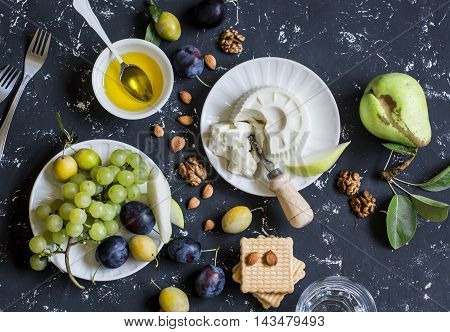 Snack table - goat cheese grapes pears plums nuts honey cracker. Top view