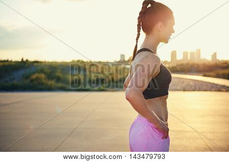 Side view of woman with ponytail and pink shorts pausing after a workout with sun glare near face and cityscape in background behind trees